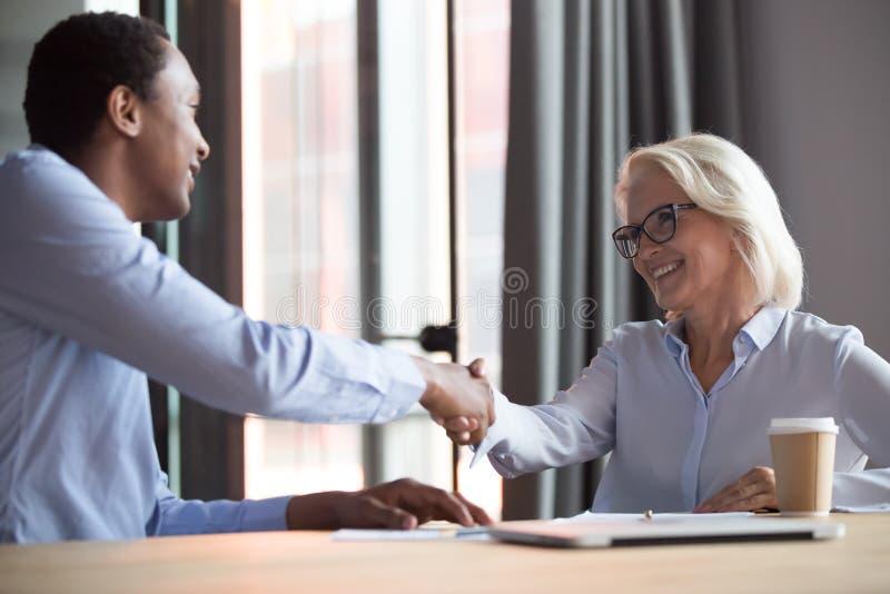 Kandidat för klient för affärsman för lycklig handskakning för affärskvinnamäklaretimme afrikansk royaltyfri foto