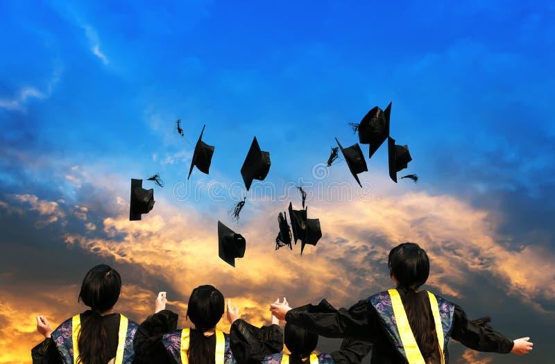 Kandidater som kastar avläggande av examenhattar royaltyfri fotografi
