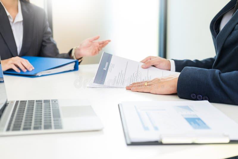 Kandidatsvar för ung man som frågar frågor till sökandet om arbete och förklarar hans profil till affärschefer som får det royaltyfri foto