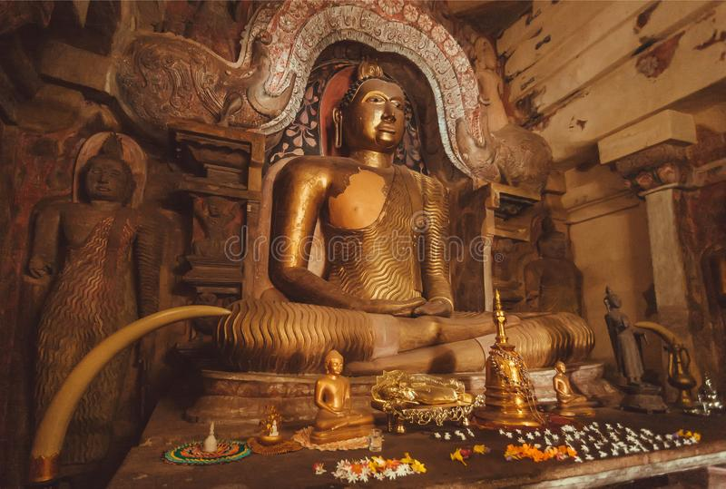 Interior of 14th century buddhist temple with stone figure of meditating Buddha in old decoration stock photo