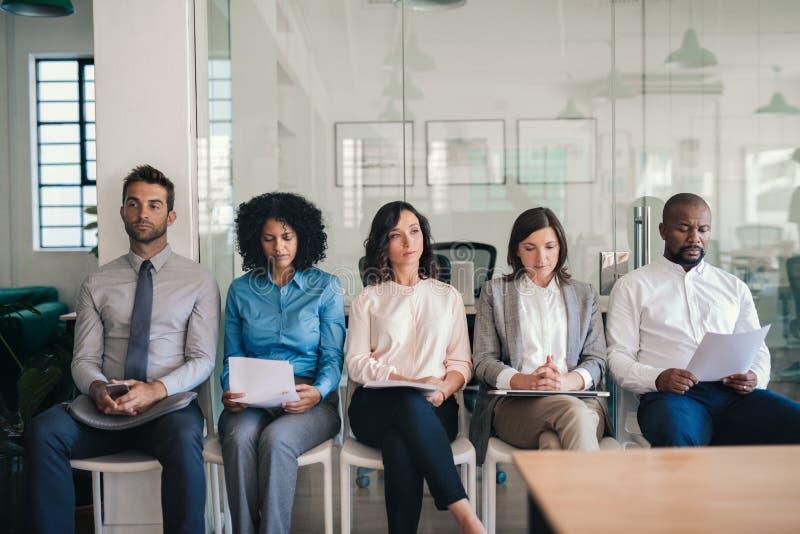 Kandydaci do pracy siedzi wpólnie w biurze czekać na wywiada obrazy royalty free