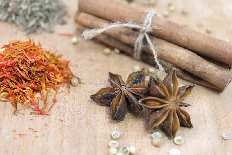 Kaneel, safron, steranijsplant en peper op een houten lijst royalty-vrije stock afbeelding