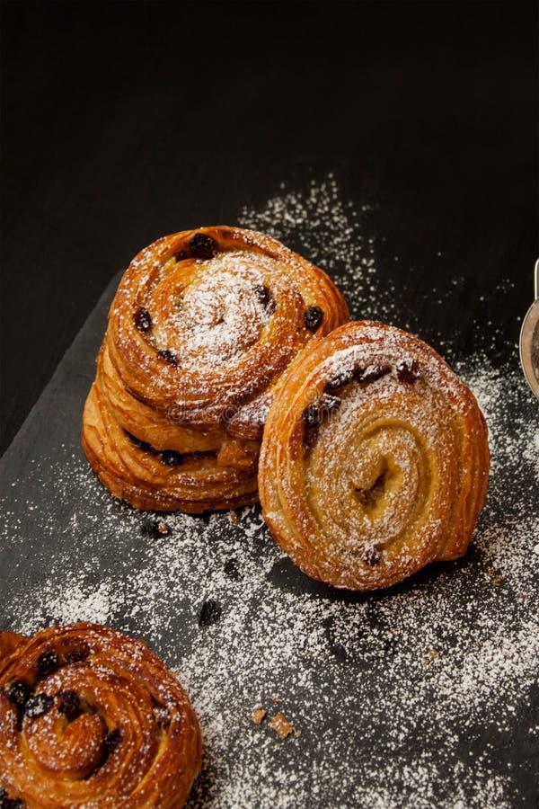 Kaneelbroodjes met suiker worden bestrooid die stock afbeeldingen