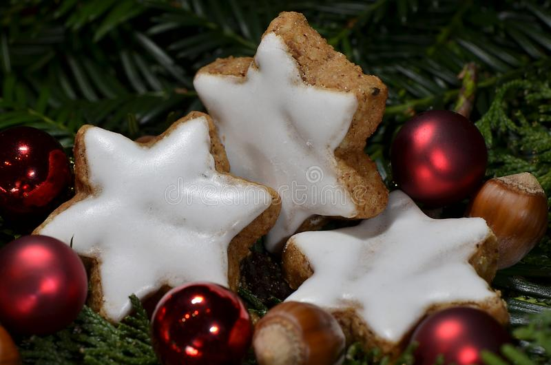 Kaneelsterren met hazelnoten en rode Kerstmisballen stock fotografie