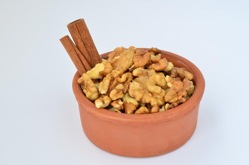 Kanel och valnötter i lerabunke arkivbild