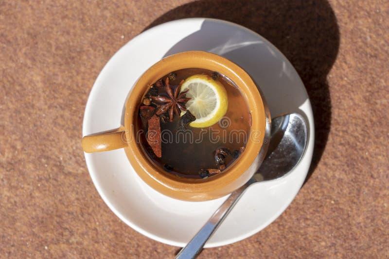 Kanelbrun toddy som består av kanel, svartpeppar, kardemumman, stjärnaanis, citronen, kryddnejlikor och varm äppelmust i gatakafé arkivfoto