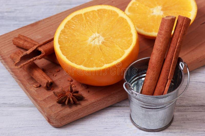 Kanelbruna pinnar i metallisk hink och skivad orange frukt på träplattan arkivbild