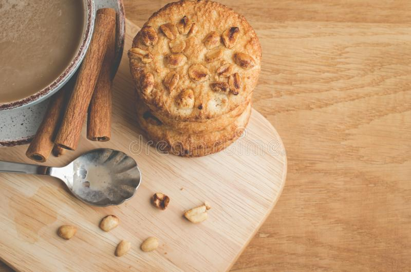 kanelbruna pinnar, kakor med muttrar och en kopp kaffe/frukost med kanelbruna pinnar, kakor med muttrar och en kopp kaffe på a fotografering för bildbyråer