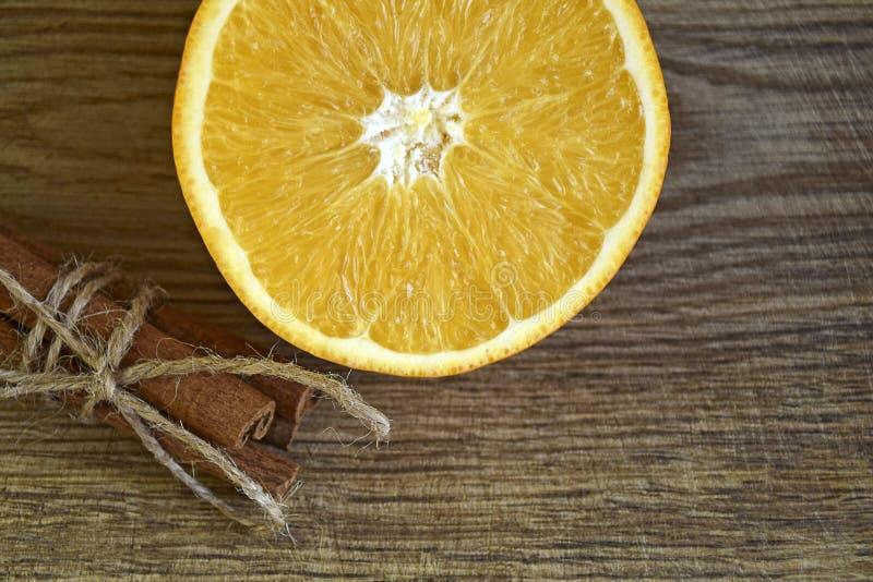 Kanelbruna pinnar och skivad ny apelsin royaltyfri fotografi