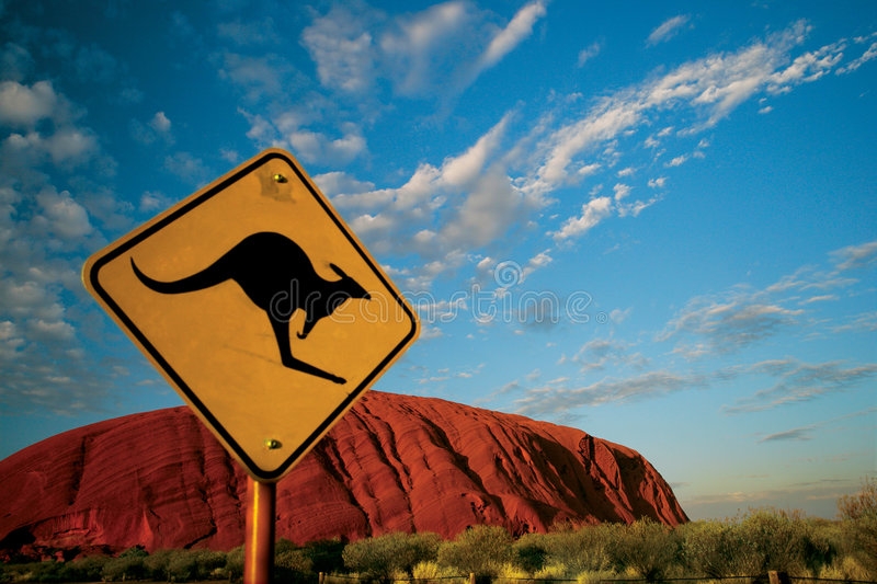 Kangaroo Ayers Rock. A slightly blurred Kangaroo warning sign in front of a focused Ayers Rock in the Australian outback stock image