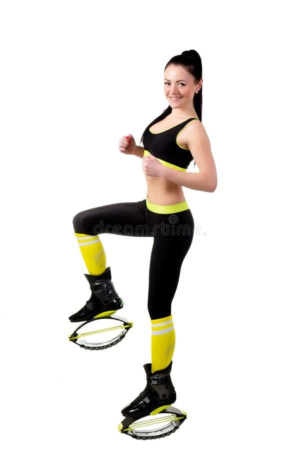 kangoo jamps的苗条微笑的女孩穿上鞋子做锻炼, 免版税库存图片