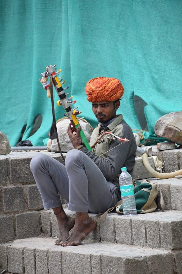 KANGRA-OMRÅDE, HIMACHAL PRADESH, INDIEN, Maj 2017, man på gatorna som spelar musik på musikalisk intrument på McLeod Ganj arkivfoto