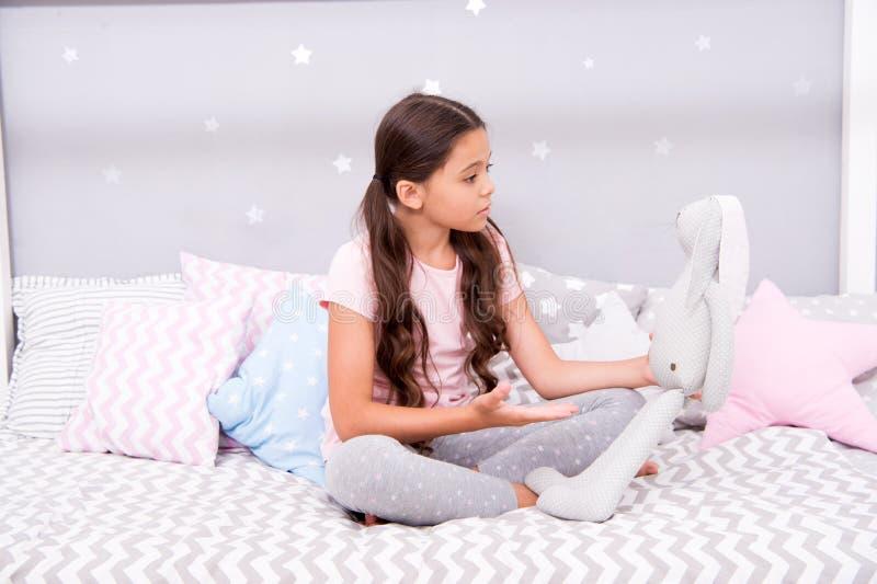 Kanin för grå färger för barnlek Bästa vän Flickan sitter säng med den gråa kaninleksaken hennes sovrum Ungen förbereder sig att  royaltyfri fotografi