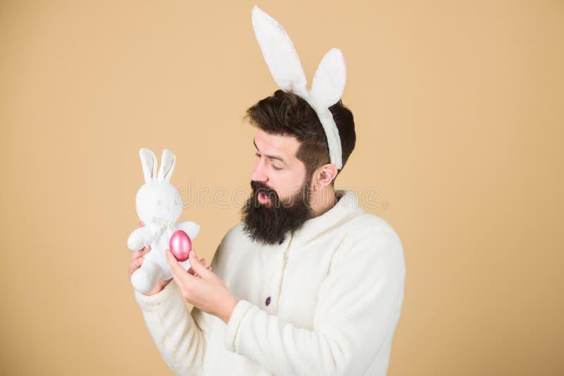 Kanin för skäggig hipster för grabb gladlynt med långa vita öron easter kanin Att bära för man oavbrutet tjata dräktlek med leksa arkivfoto
