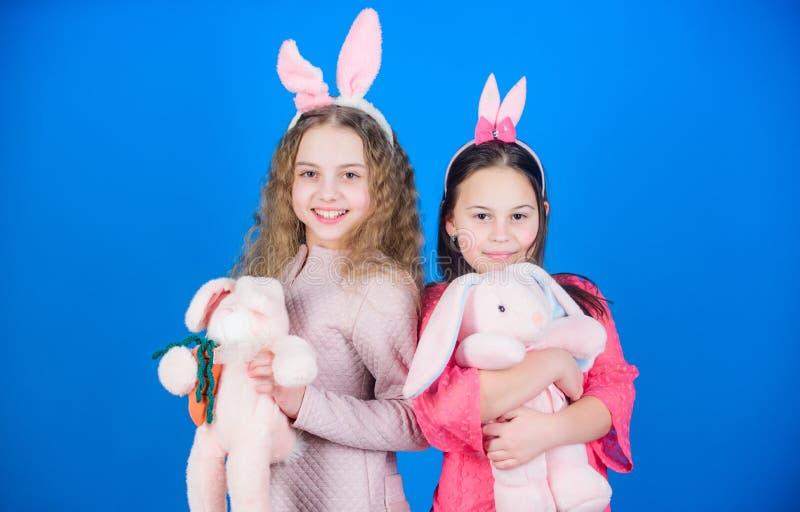 Kanin för kanin som family Barn i kaninkaninöron Äggjakt Familj och systerskap Små flickor med hareleksaken Isolerat på vit bakgr royaltyfria bilder