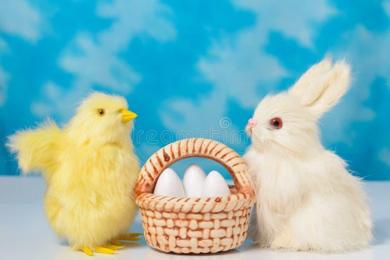 Kanin och fågelunge med korgen av påskägg på en bakgrund av blå himmel royaltyfria foton