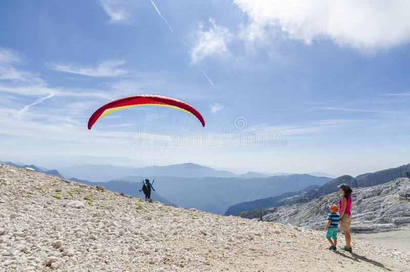 2018-09-12 Kanin, Slovenia. Mother and son watch the paraglider pilot take off high in the mountains stock image
