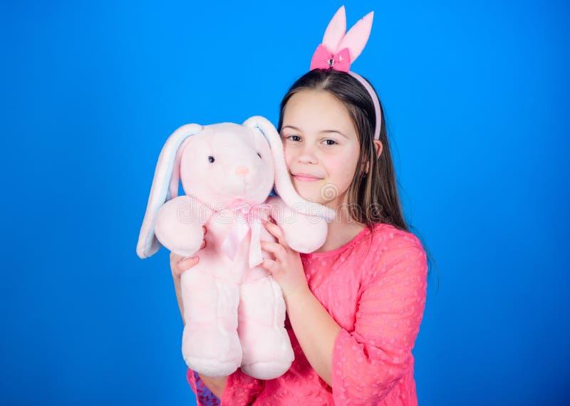 Kaninen gå i ax tillbehören Det älskvärda skämtsamma kaninbarnet kramar den mjuka leksaken Kaninflicka med den gulliga leksaken p fotografering för bildbyråer