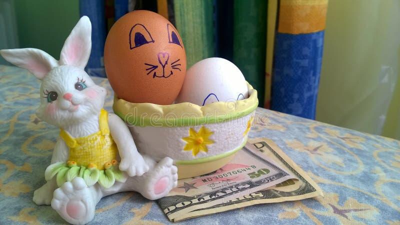Kaninen leker med easter ägg och pappers- dollar fotografering för bildbyråer