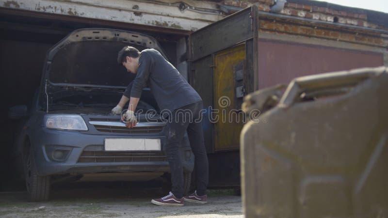 Kanisterställningar av den unga mannen reparerar framme bilen i garage arkivfoton