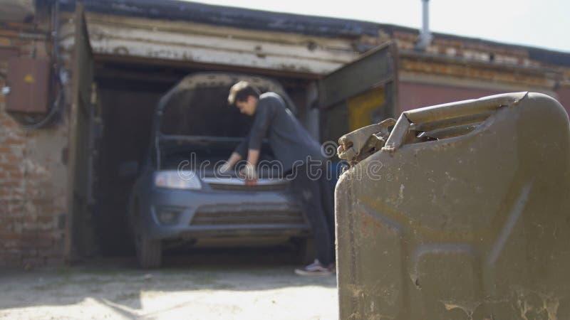 Kanisterställningar av den unga mannen reparerar framme bilen i garage arkivfoto