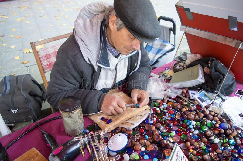 Craftman making decoration on crystal using a high speed rotary multi tool in Kaniv, Ukraine on Octob. KANIV, UKRAINE - OCTOBER 14: Craftman making decoration on stock photos