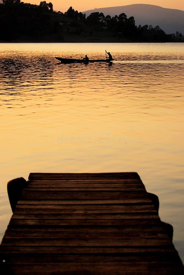 Kano op meer bij zonsondergang stock foto's
