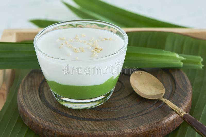`Kanom Peak Poon Bai Tuey Kati Sod` Thai Sweet. Sweet Pudding, Natural Green Color From Pandan Leaf And Topping With Coconut Milk Cream And Saseme stock photo