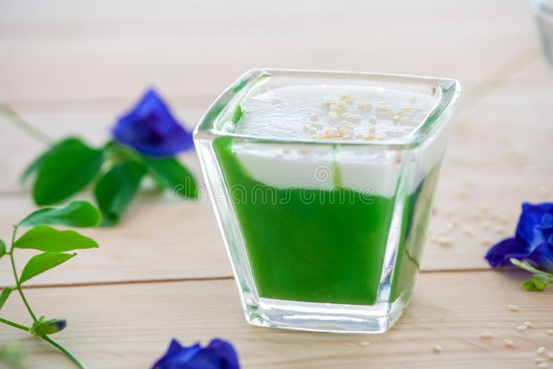 `Kanom Peak Poon Bai Tuey Kati Sod` Thai Sweet. Sweet Pudding, Natural Green Color From Pandan Leaf And Topping With Coconut Milk Cream And Saseme royalty free stock image