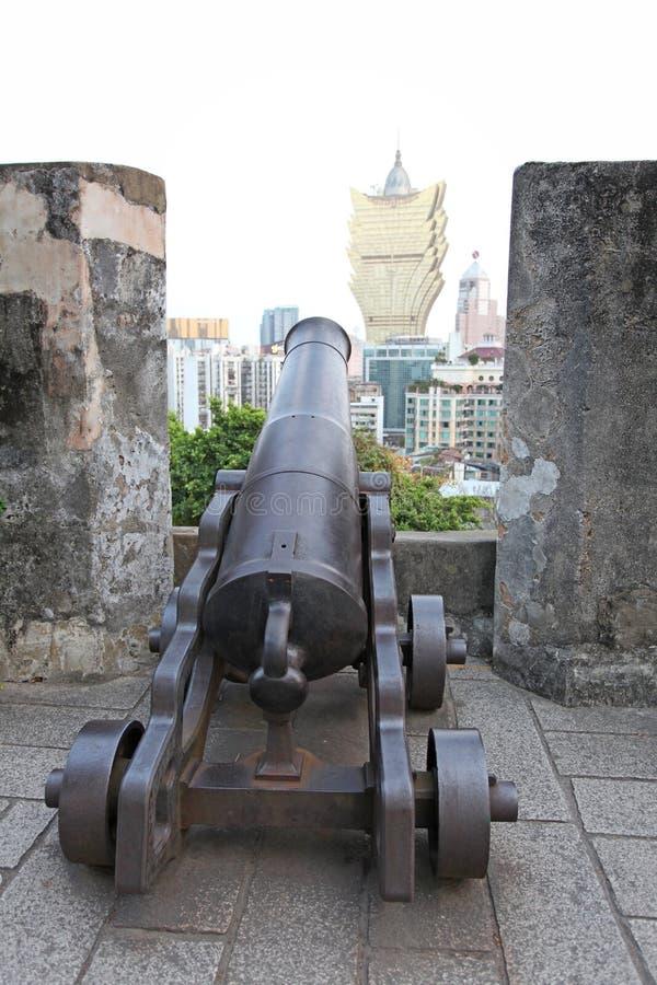 Kanon i den portugisiska fästningen Guia i Macao med den storslagna Lissabon kasinot royaltyfri fotografi