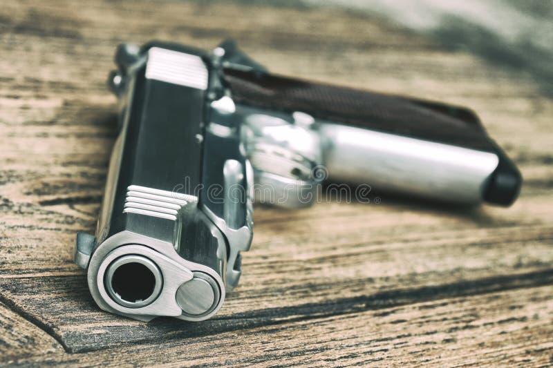 Kanonenrohr, 1911 vorbildlich, halbautomatische Pistole auf hölzernem Hintergrund lizenzfreies stockbild