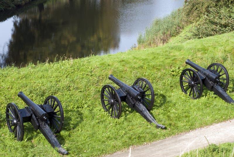 kanoner tre som väntar royaltyfria foton