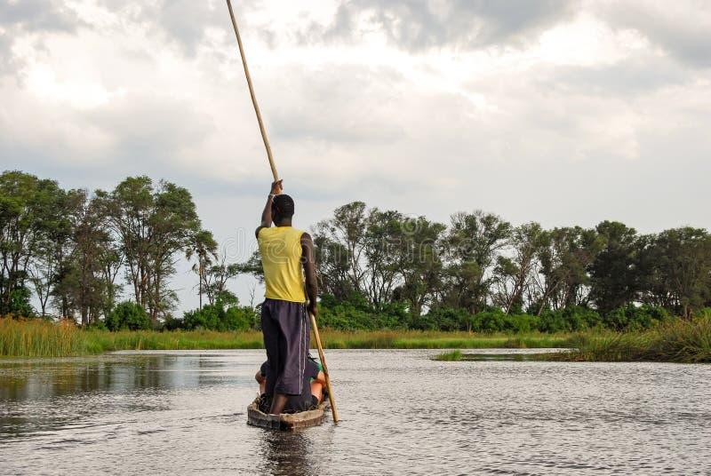 Kanoreis met traditionele mokoroboot op rivier door Okavango-Delta dichtbij Maun, Botswana Afrika royalty-vrije stock afbeelding
