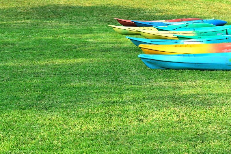 Kanota det många färgrika ordnat på gräsmattan Från vatten som ska torkas arkivfoton