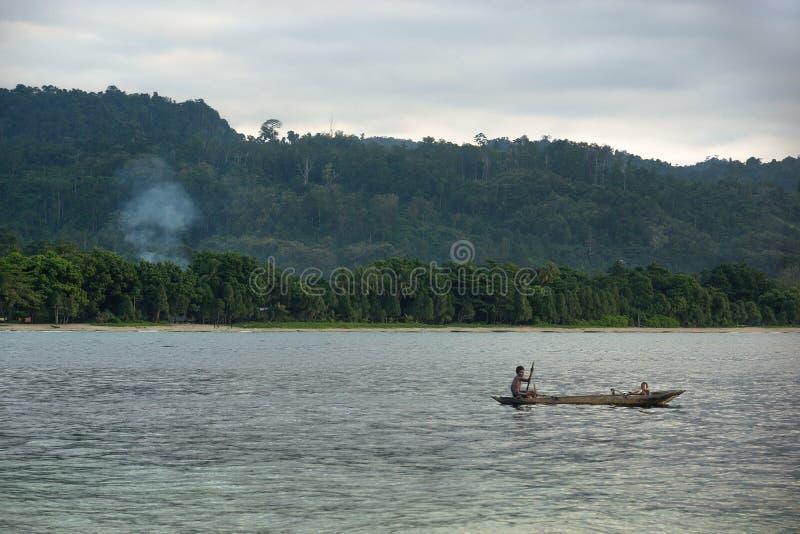 Kanoten med den papuan mannen arkivfoto