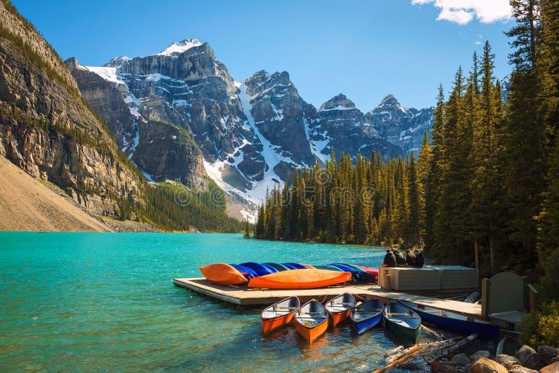Kanoter på en brygga på morän sjön i den Banff nationalparken, Kanada arkivbilder