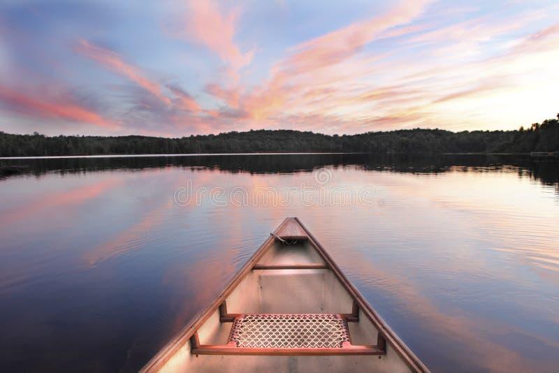 Kanotpilbåge på en sjö på solnedgången arkivfoton