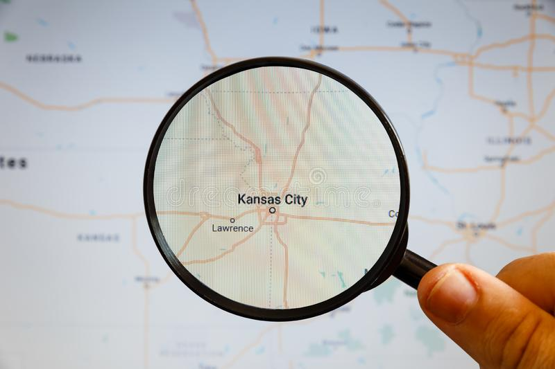 Kansas City, United States. Political map. The city on the monitor screen through a magnifying glass in hand stock image