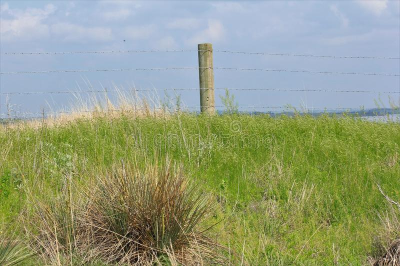 Kansas Country Fence with grass and blue sky. stock photo