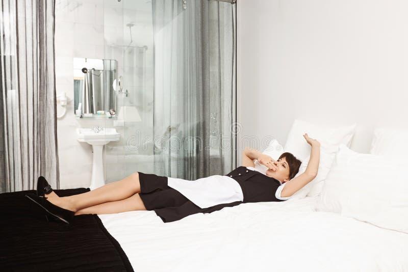 Kanske bör jag ta ta sig en tupplur, för klienter kommer Skott av den trötta kvinnan i hembiträdelikformign som ligger på säng oc royaltyfri fotografi
