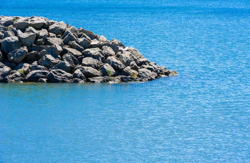 Kant av den steniga breakwalländelsen i vatten arkivfoton