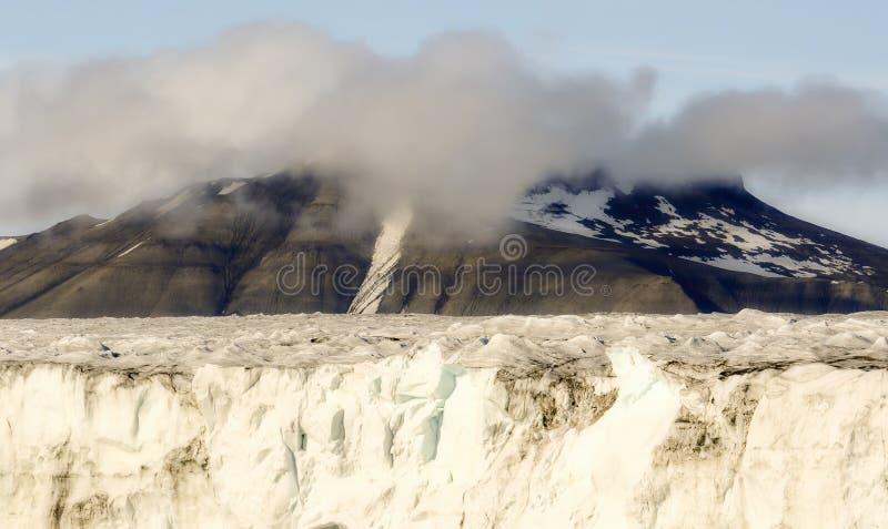 Kant av en glaciär med ispacken och dimmigt som är molniga, korkade berg för snö royaltyfri bild