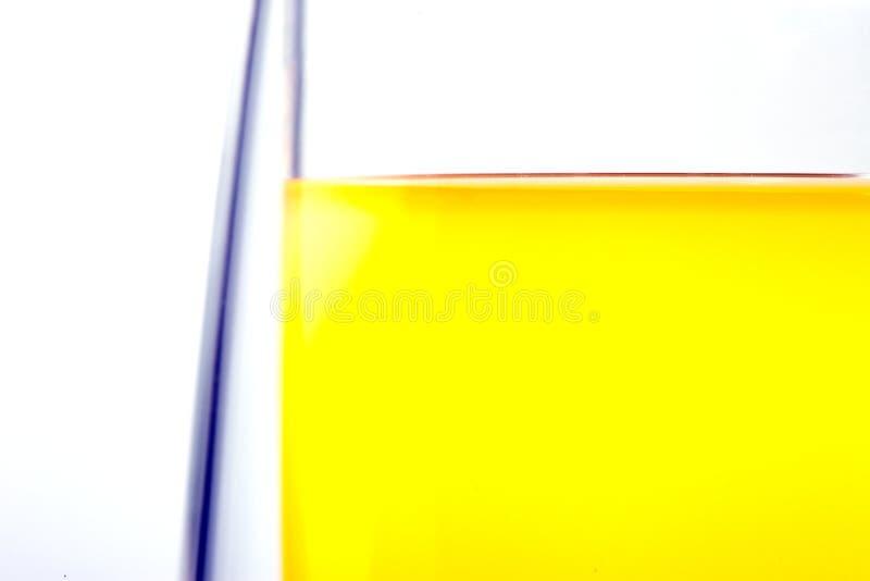 Kant av ett exponeringsglas med en drink på en vit bakgrund arkivbilder