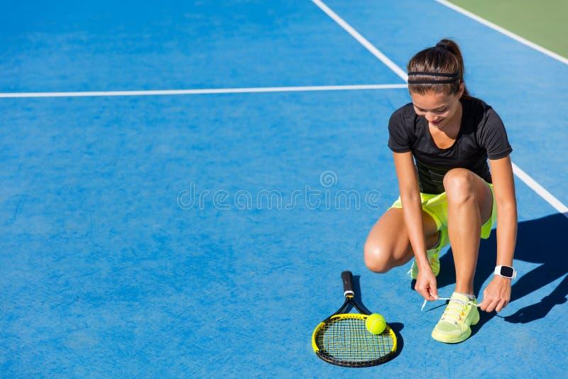 Kant van de de vrouwen het bindende schoen van de tennisspeler op hof stock afbeeldingen