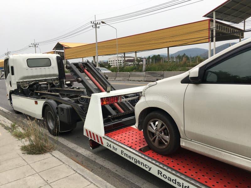 Kant van de weghulp gebroken auto op een slepenvrachtwagen op een kant van de weg royalty-vrije stock foto