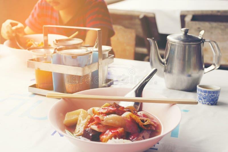 Kant van de wegrestaurant van Azië met Thaise noedels en achtergrond van jongen die zijn noedel op lijst eten stock afbeelding