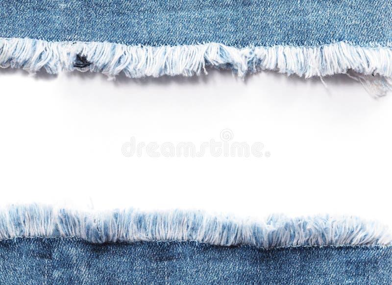 Kanta ramen av blå grov bomullstvilljeans som rivas sönder över vit bakgrund royaltyfri foto