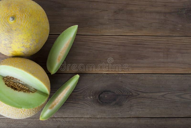 Kantaloep gele verse die meloen met gesneden meloen, houten lijst, grijze achtergrond wordt geïsoleerd De zomervruchten De ruimte stock afbeelding