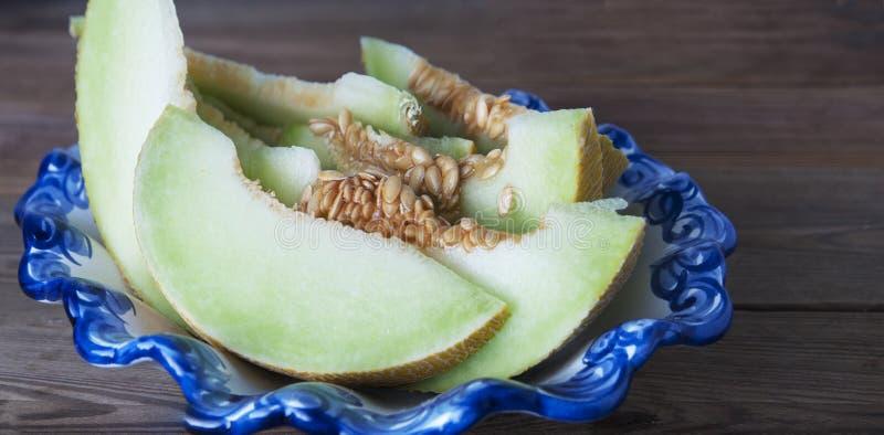 Kantaloep gele verse die meloen met gesneden meloen wordt geïsoleerd, in mooie uitstekende blauwe plaat, houten lijst, grijze ach stock foto
