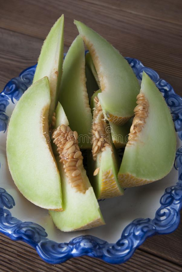 Kantaloep gele verse die meloen met gesneden meloen wordt geïsoleerd, in mooie uitstekende blauwe plaat, houten lijstachtergrond  stock foto